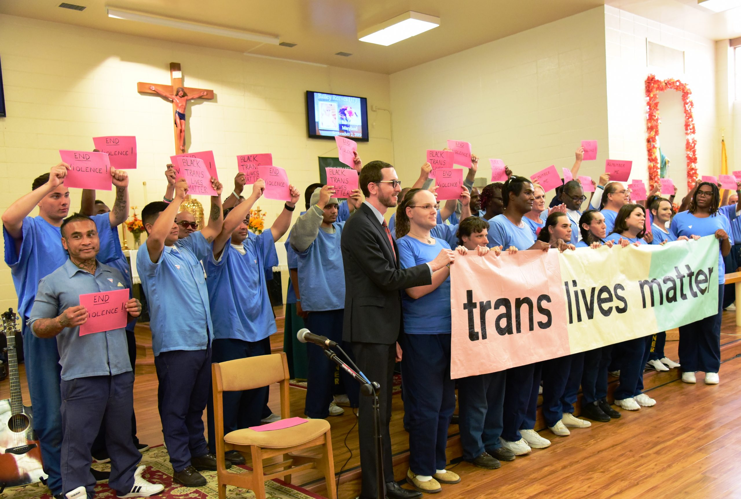 Group of people standing and holding sign that states trans lives matter