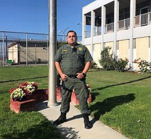Officer stands near a flag pole.