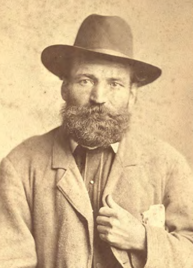 Man with bushy beard wears a hat and stares at the camera.