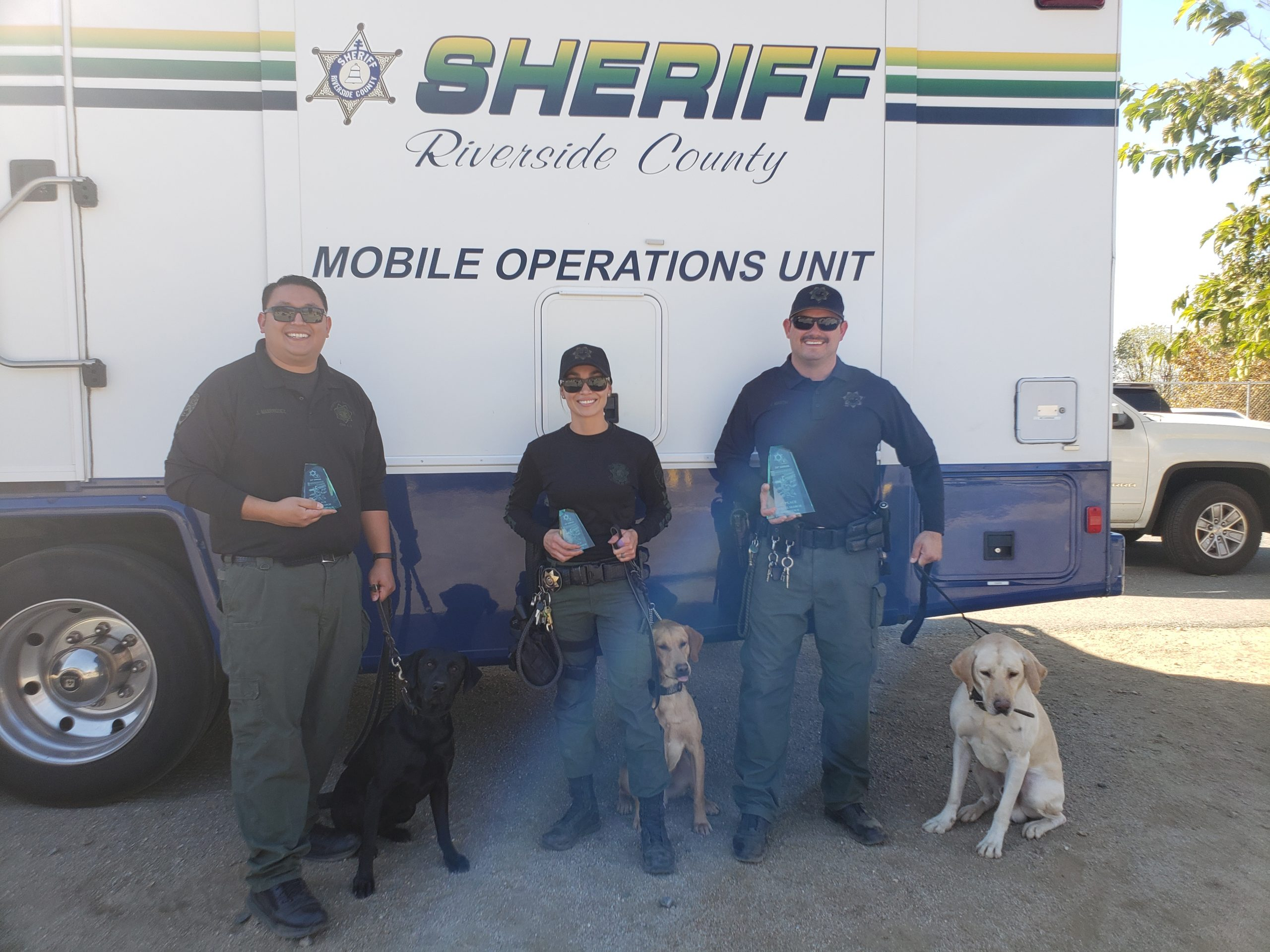 Three officers and their dogs stand in front of a Riverside County Sheriff mobile operations unit van.