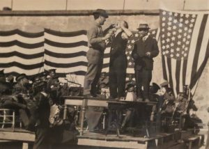 Magician Harry Houdini stands on a makeshift stage in San Quentin prison. He's flanked by two other men.