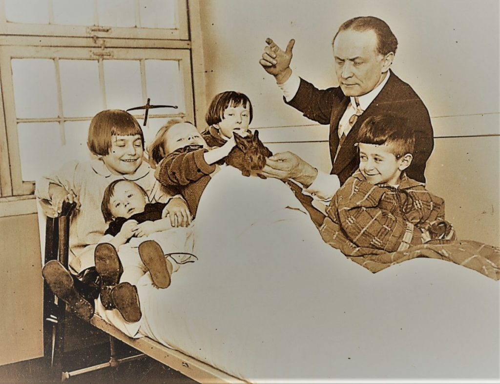 Harry Houdini performs for children in a hospital.