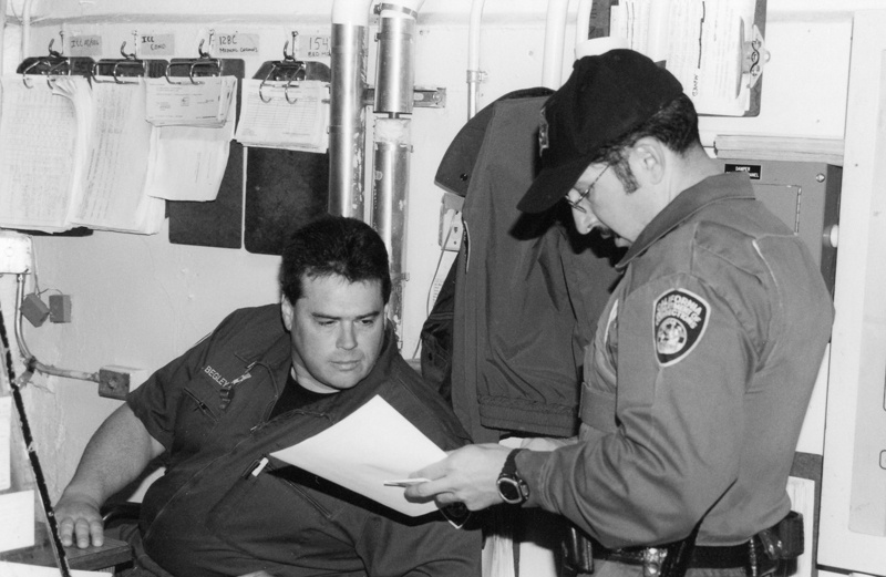 Two officers look at a piece of paper.