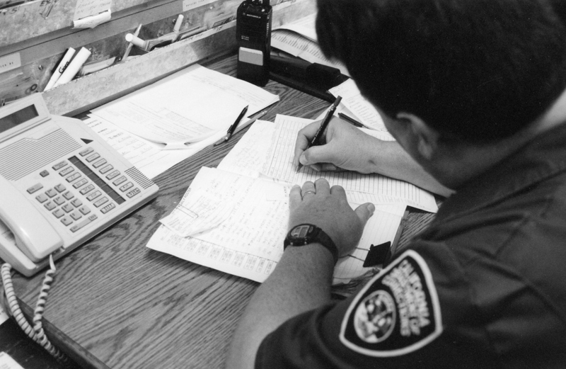 Officer fills out a form at his desk.