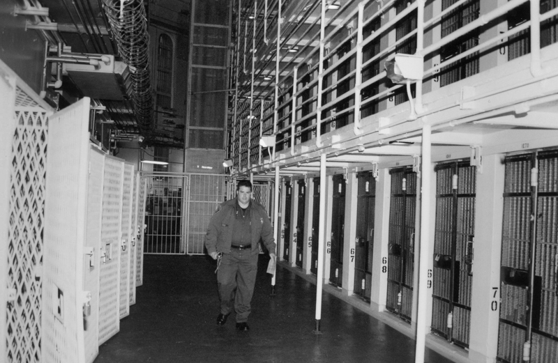 Black-and-white photo of officer walking along a cell block.