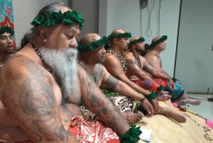 Asian and Pacific Islander men sitting on the floor with green crown and red printed skirt