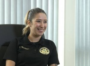 Smiling woman wears dark shirt with a badge logo on it and the name V. Melendez.