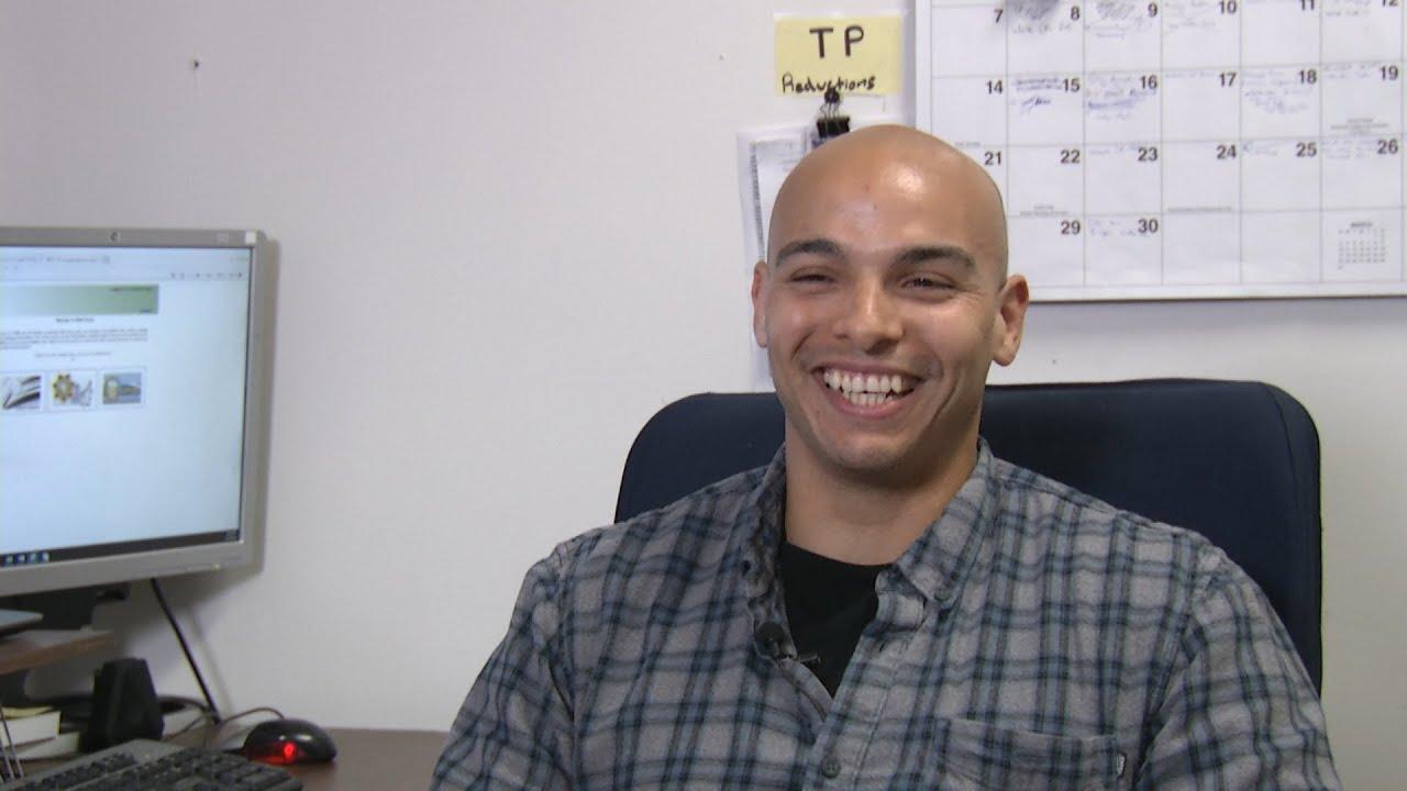 Man sits at computer desk.