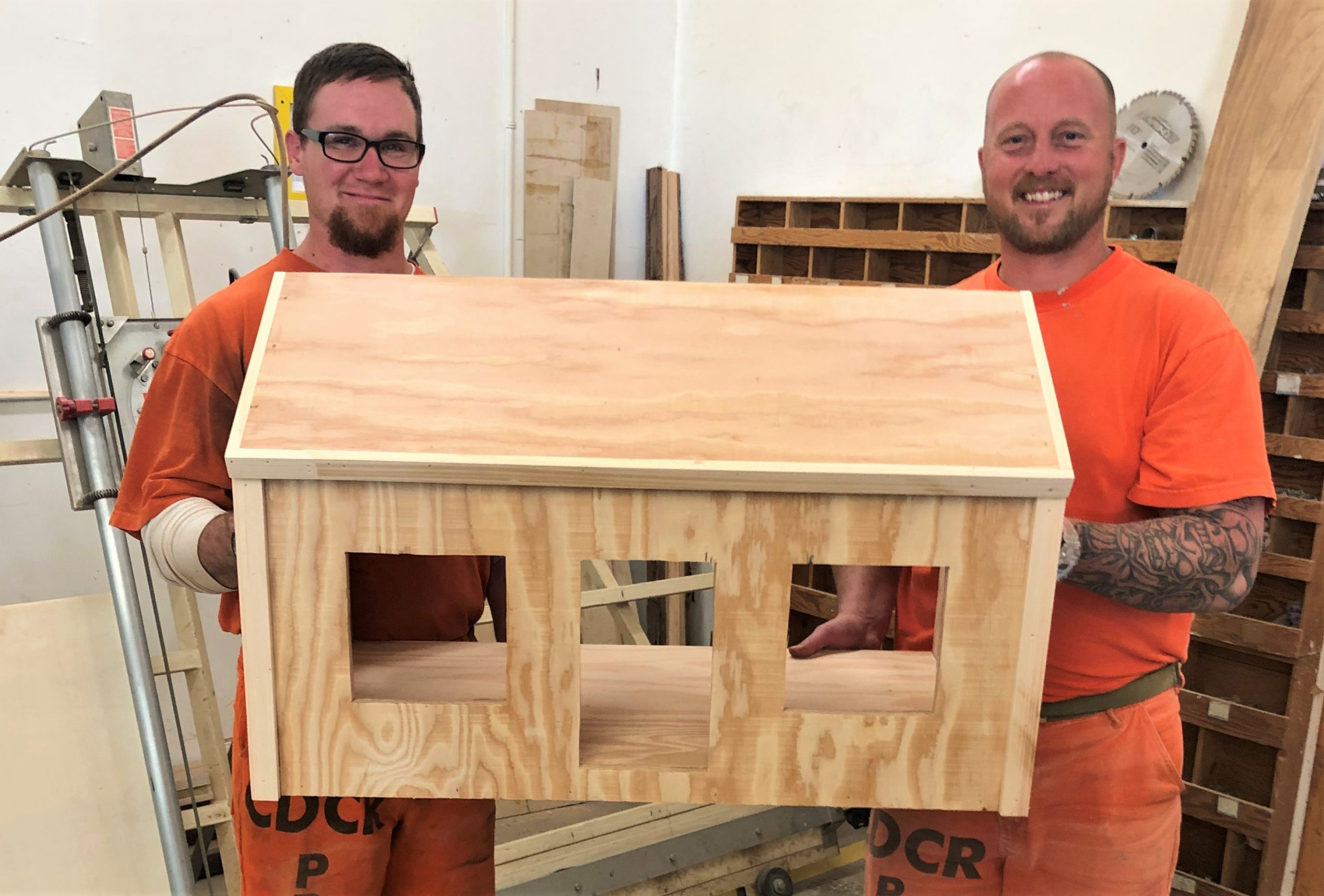 Two inmates hold a large dollhouse.