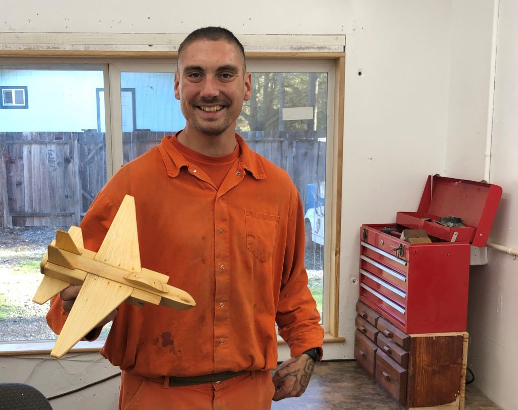 Inmate holds a toy wooden plane.