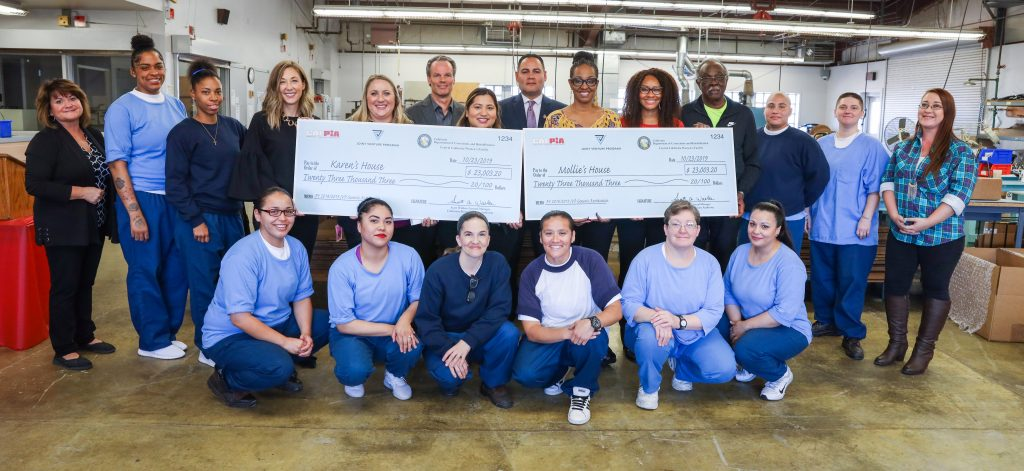 Female inmates and others pose with two large oversized checks.