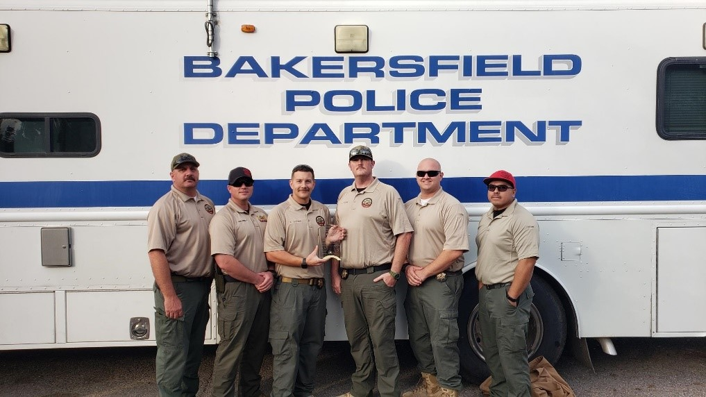 Correctional staff in front of a Bakersfield Police Department command center mobile unit.