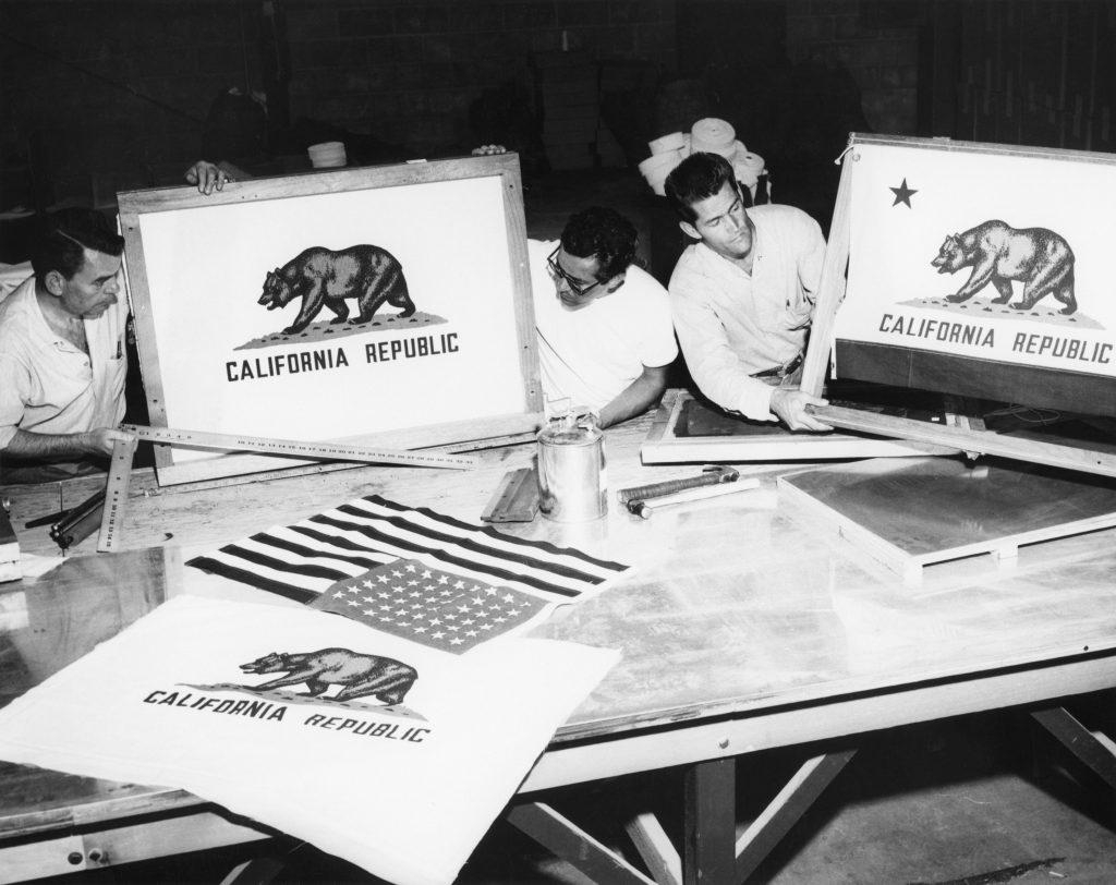 Men create flags through silk screening.