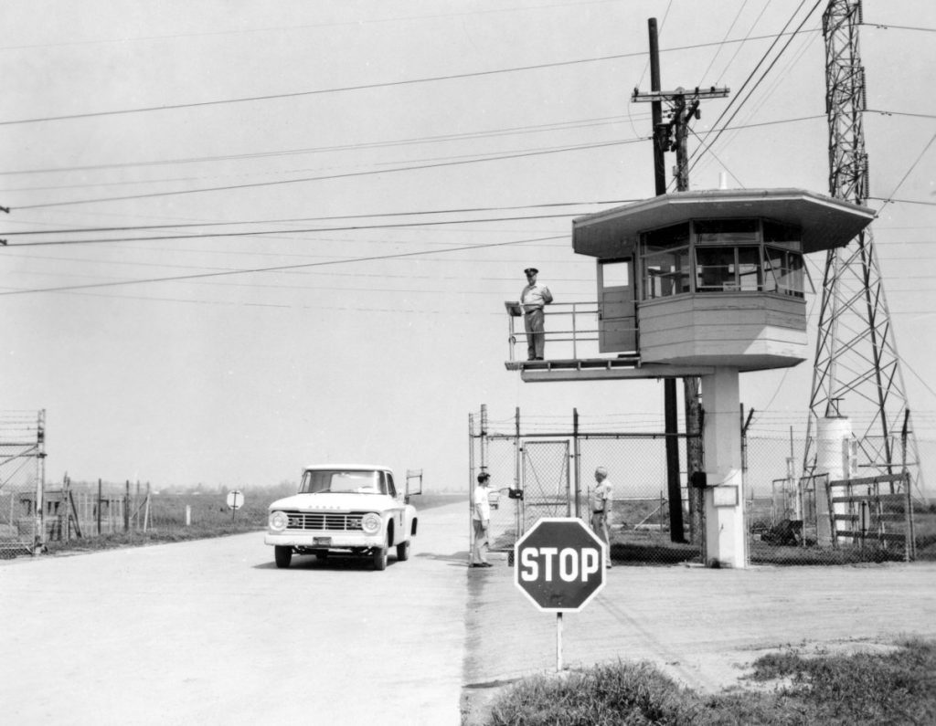 Prison tower and men at a gate with a  1950s pickup truck in the background.