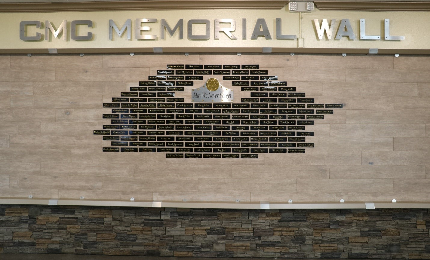 """A wall with small name plaques and the words """"CMC Memorial Wall"""" across the top."""