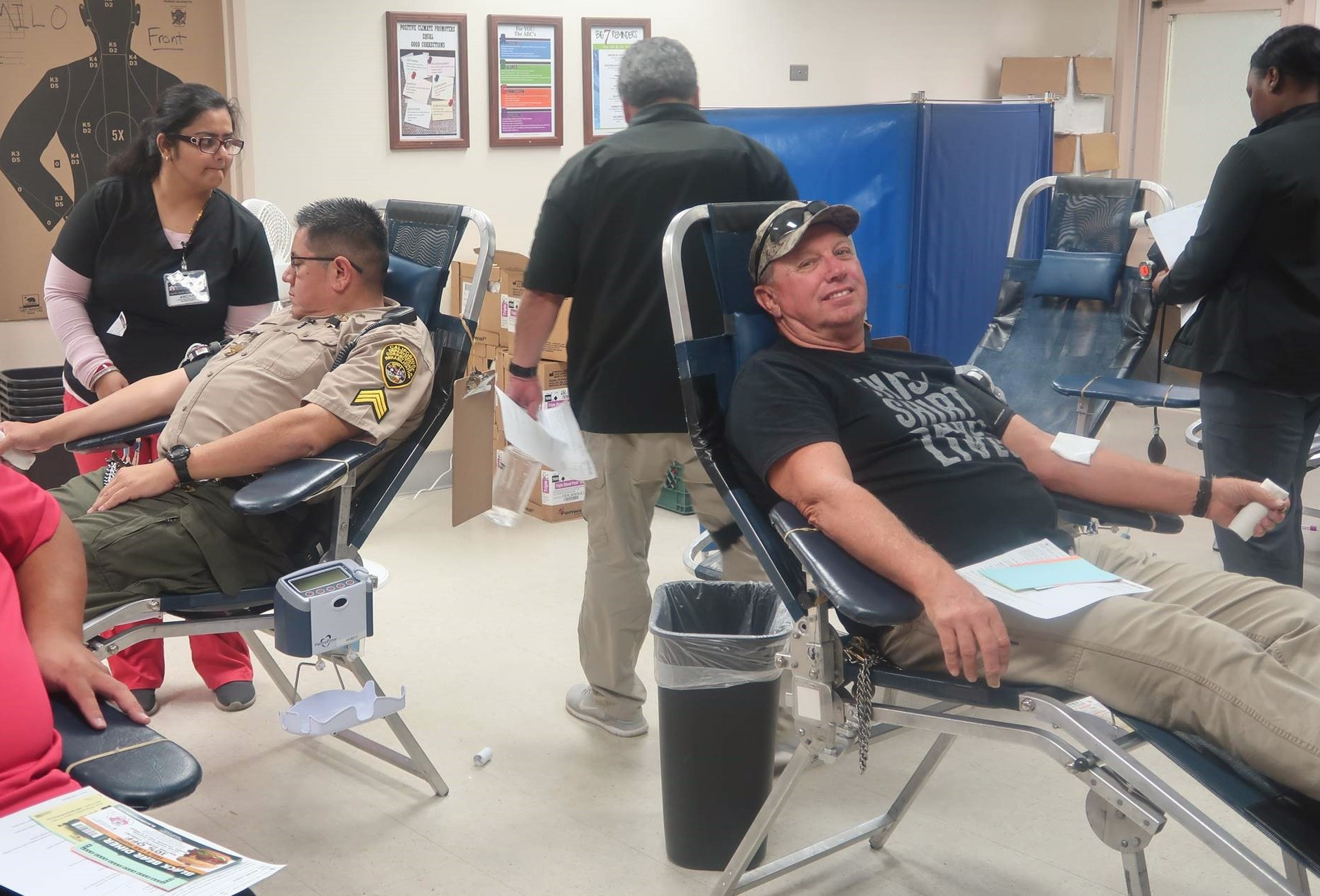 Two men lie down to donate blood.