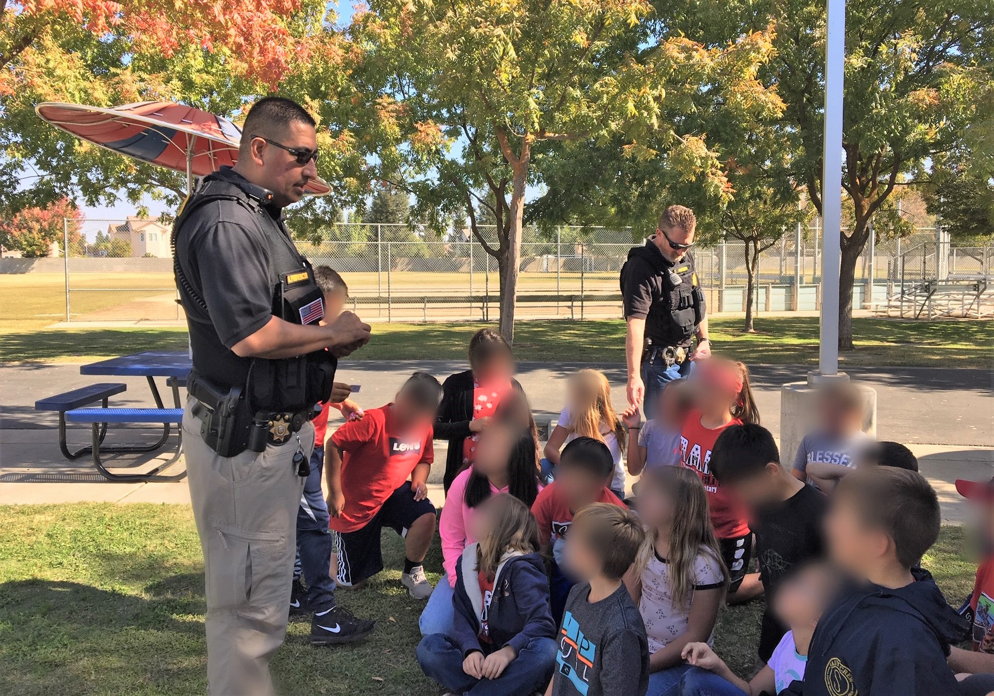 Men in uniforms talk to kids.