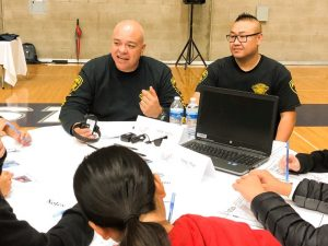 Two parole agents sit at a table with high school students in Clovis.