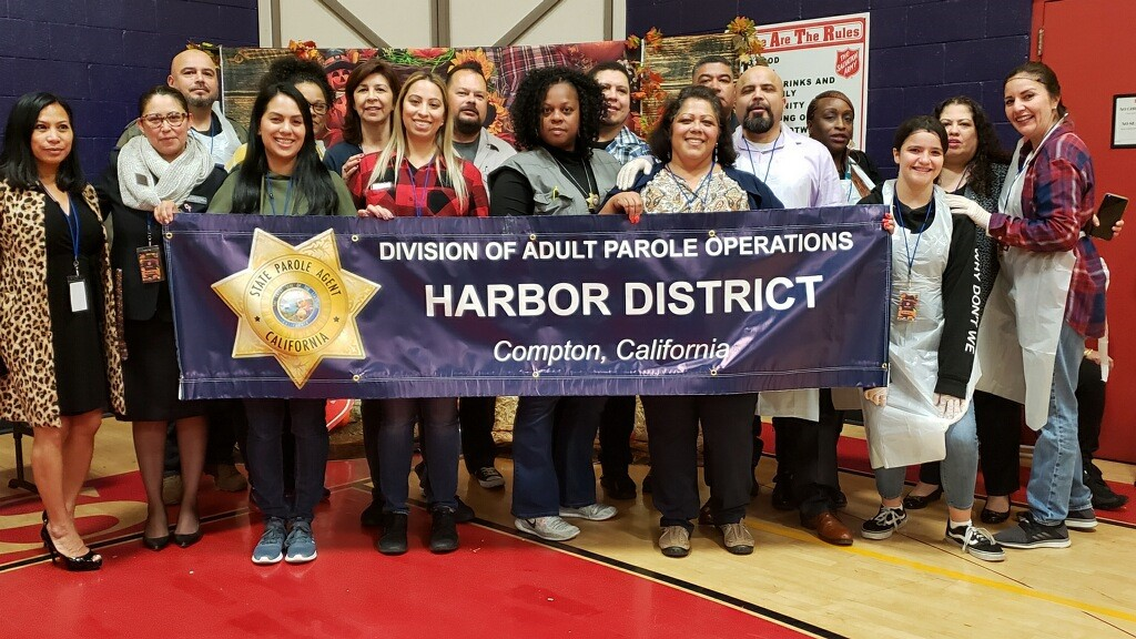 Men and women stand behind a banner that reads Division of Adult Parole Operations Harbor District, Compton, California.