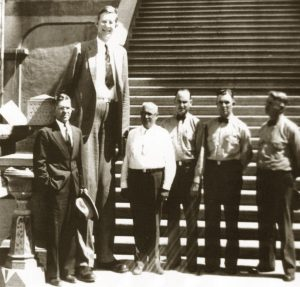 Robert Wadlow towers over five other people in front of Folsom prison.