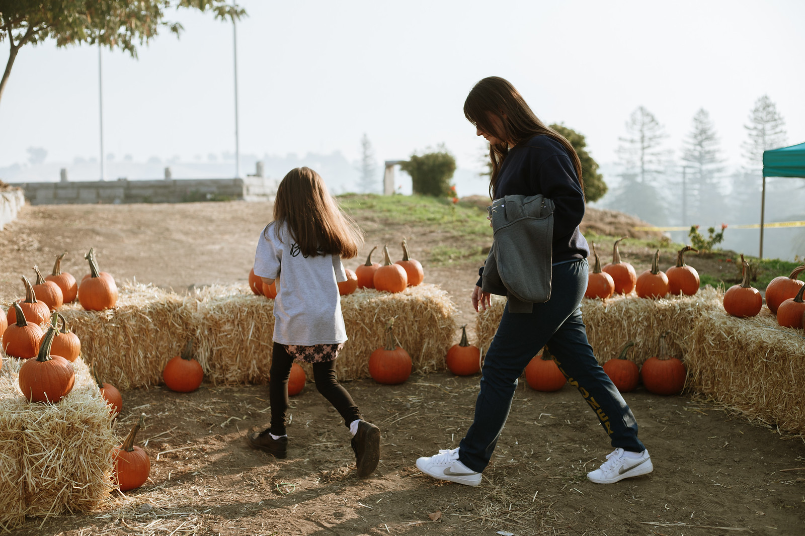 Woman and girl walk in front of pumpkins with prison walls in the background.