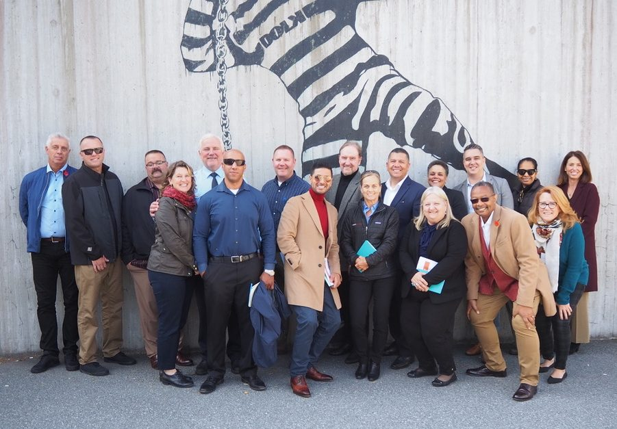 California prison officials stand in front of a mural depicting a prison inmate wearing a striped uniform.