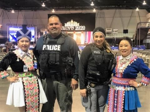 Parole agents pose with women in traditional Hmong outfits.