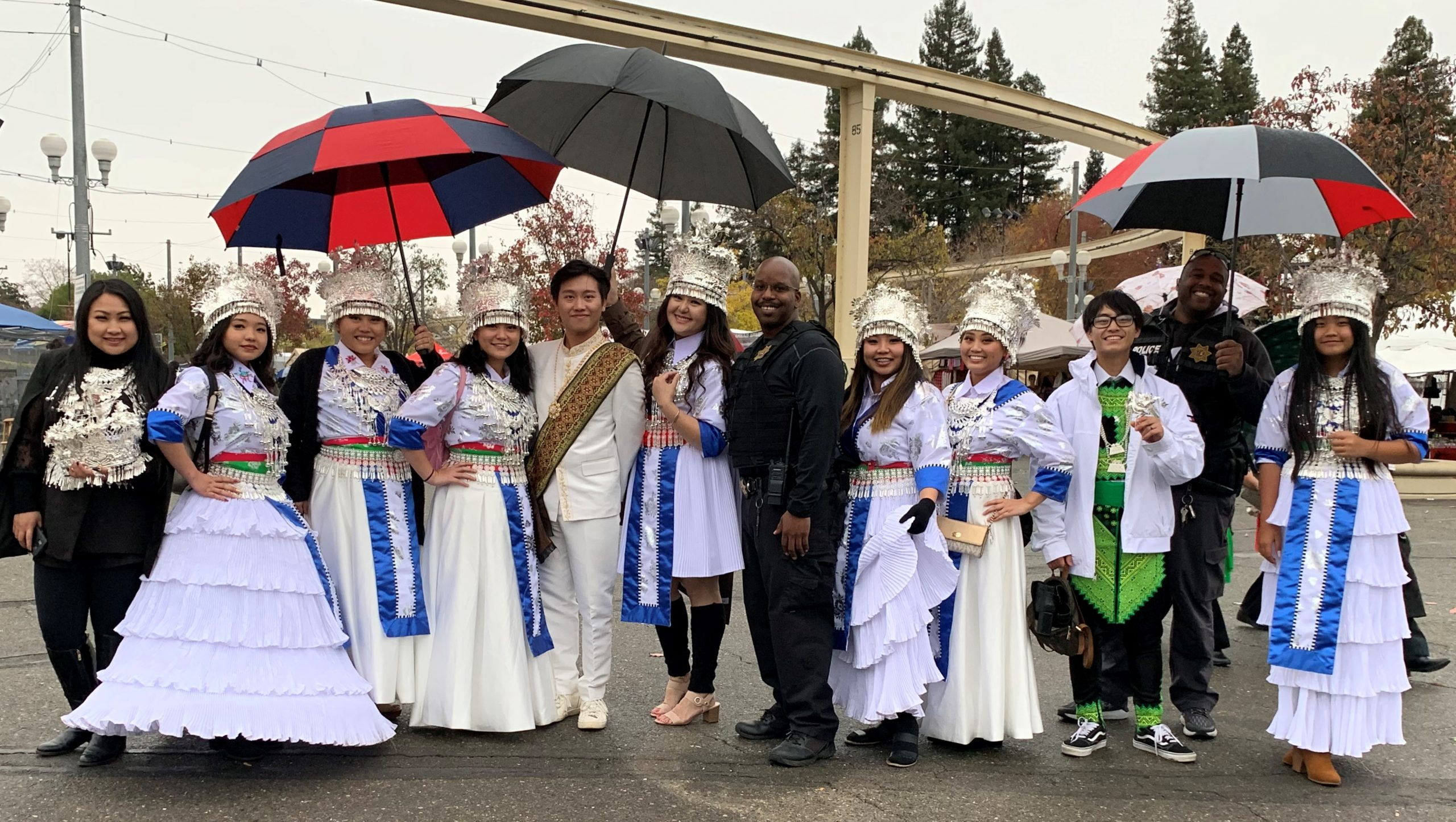 Two officers stand with Hmong women in traditional dresses.