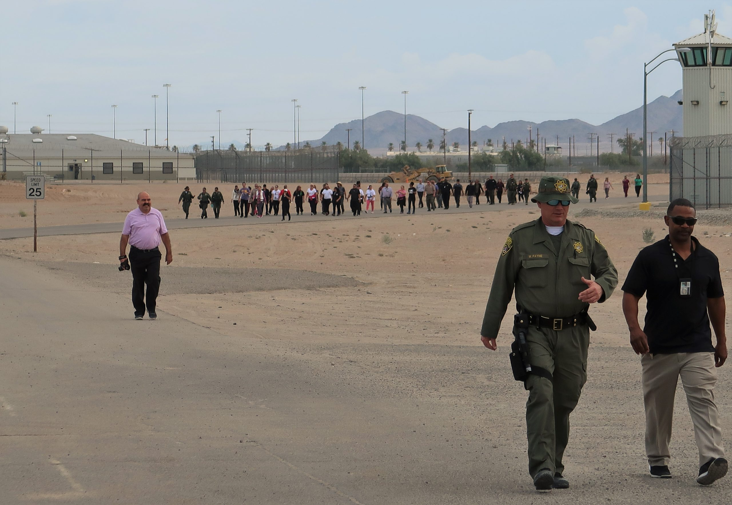 People walk on prison grounds.