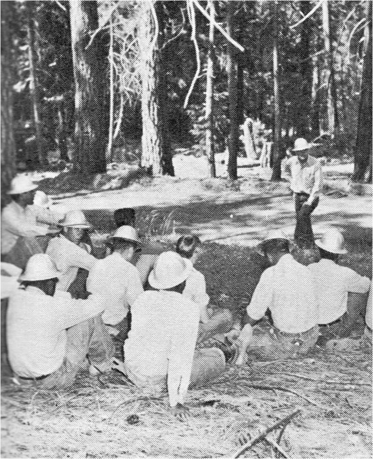 1961 black and white photo of inmates sitting on ground listening to an instructor surrounded by trees