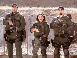 Two men flank a woman. All are wearing military style clothing.