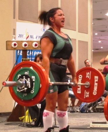 Woman lifts weights.