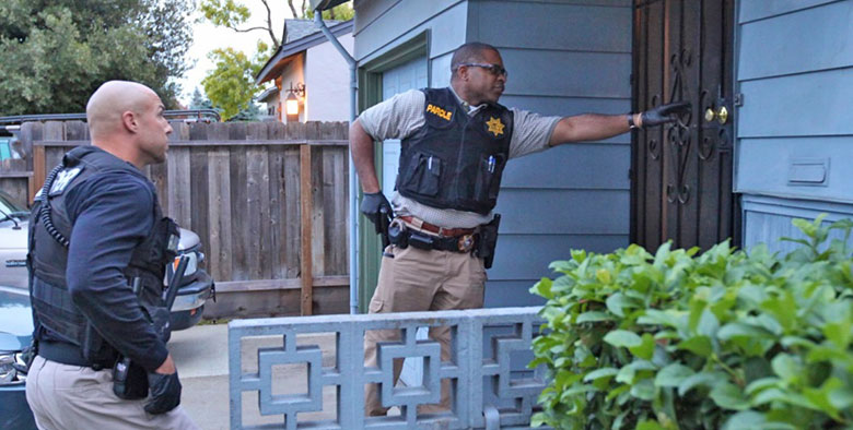 A parole agent knocks on a door while another agent waits nearby.