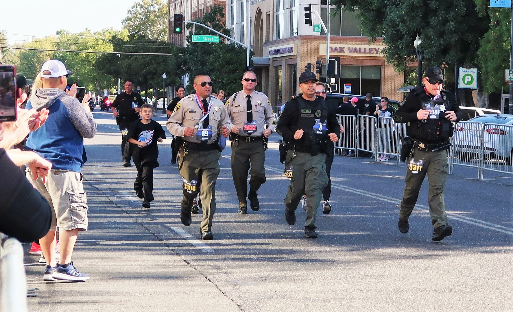 Correctional staff run on a street as people cheer from the sidewalks.
