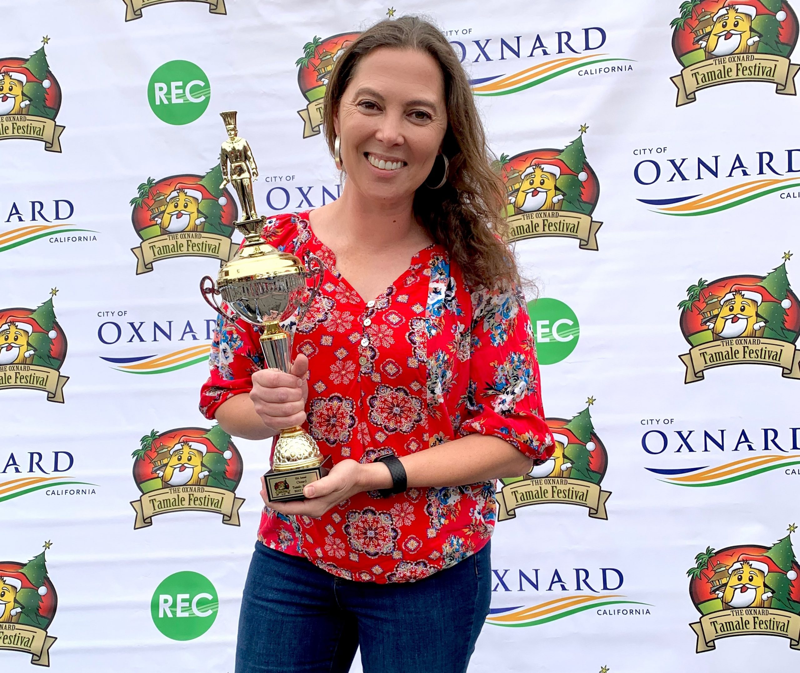 Woman smiling and holding a trophy