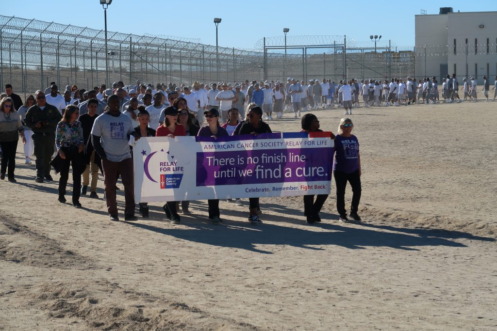 Inmates and staff walk in a prison yard.