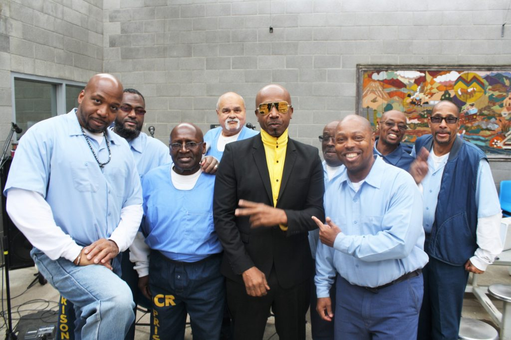 MC Hammer poses with inmates in a prison.