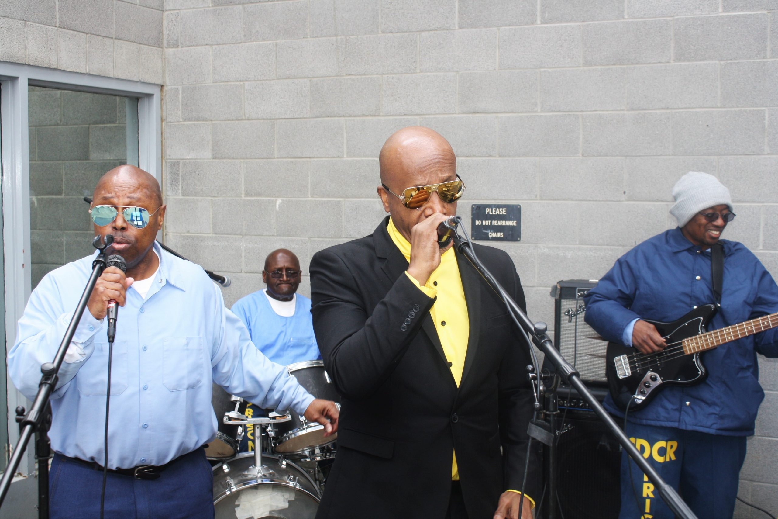 Singer MC Hammer sings into a microphone with inmates play instruments and sing backup.