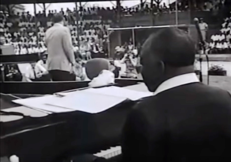 Inmates sit in bleachers while watching Frank Sinatra and Count Basie perform.