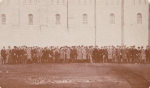 People stand in front of a San Quentin prison building.