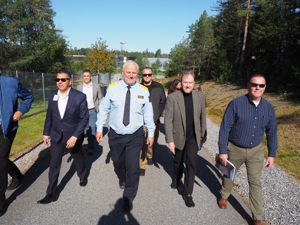 California prison staff walk with Norway prison officials on a paved walkway surrounded by trees.