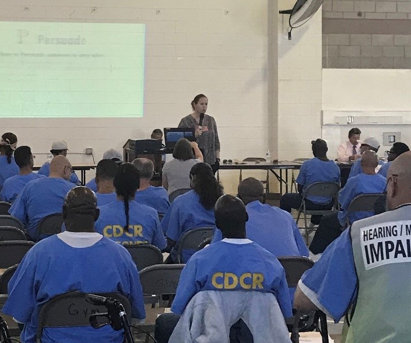 Group of inmates sit while someone speaks into a microphone.