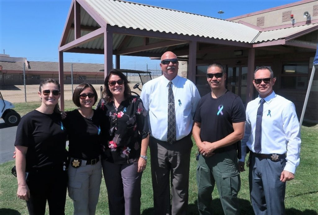 Prison staff wear suicide awareness ribbons on their shirts.