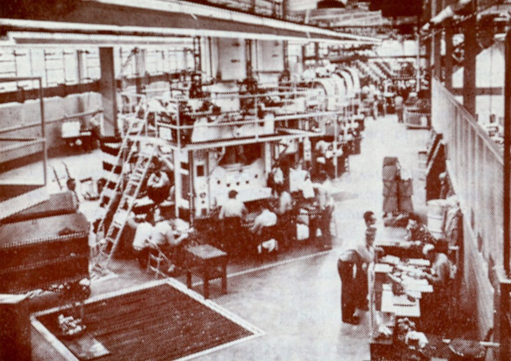 Large stamping machines in a warehouse-like structure.