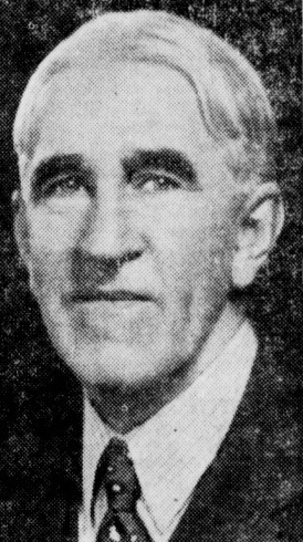 Grainy black and white photo of a man wearing a suit and tie.