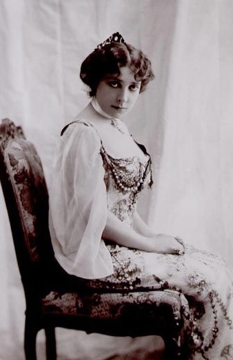Woman in beaded gown sits on a chair, staring into the camera.