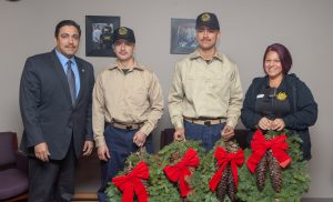 Two fire camp youth hold wreaths while a parole agent and the CDCR executive stand on either side.