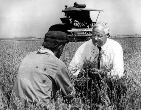 Man kneels in a field with an inmate while large harvesting combine in the background.