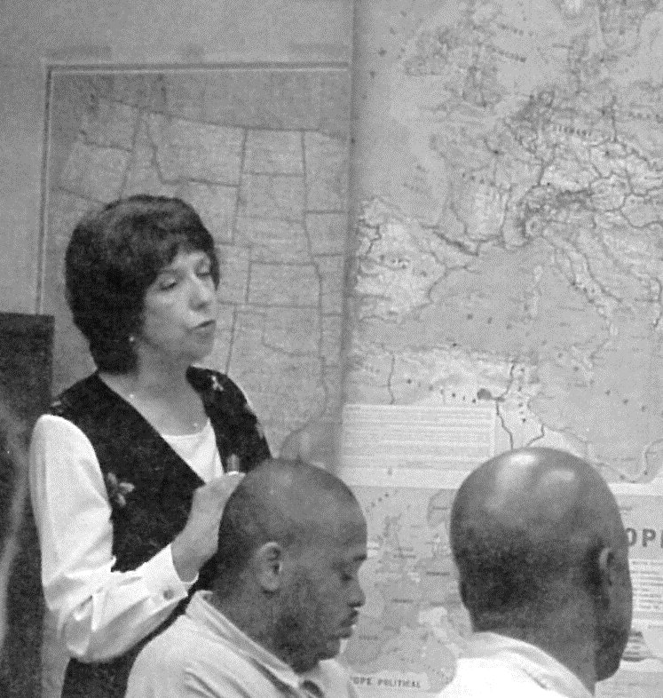 Woman speaks in front of a map hanging on the wall while adult inmates listen.