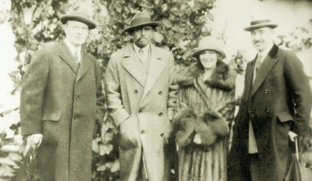 Three men and a woman all wear hats and stand in front of a prison building.